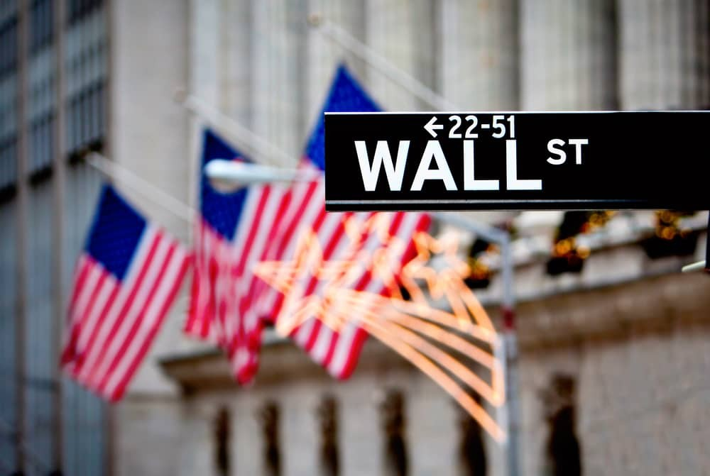 Wall-street-sign-in-New-York-with-New-York-Stock-Exchange-background